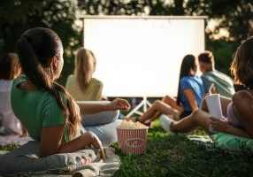 Young,People,With,Popcorn,Watching,Movie,In,Open,Air,Cinema.
